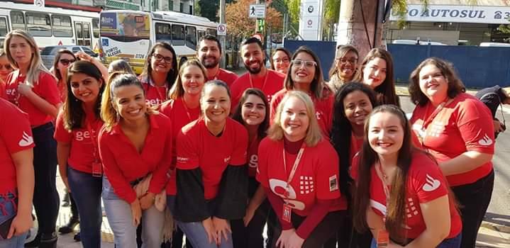 Foto com vários colaboradores Getnet vestindo camiseta vermelha. Evelyn em pé, no canto direito da foto.