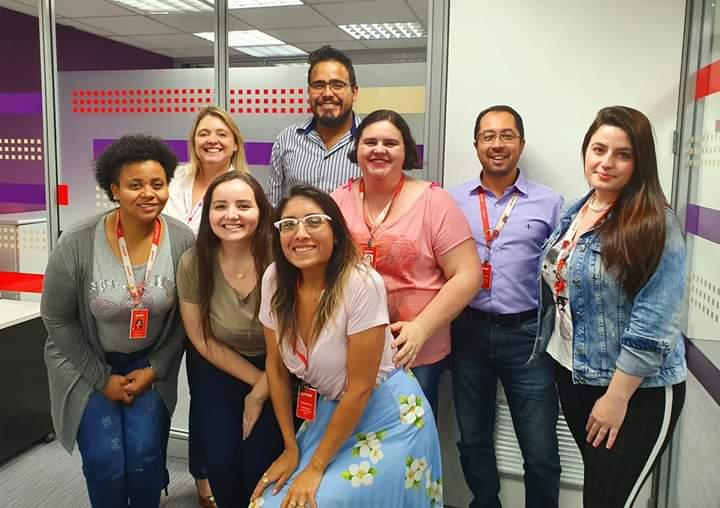 Foto tirada no interior da Getnet, com homens e mulheres, colaboradores e gestores da empresa Getnet, alguns em pé, outros agachados, ao lado da Evelyn.