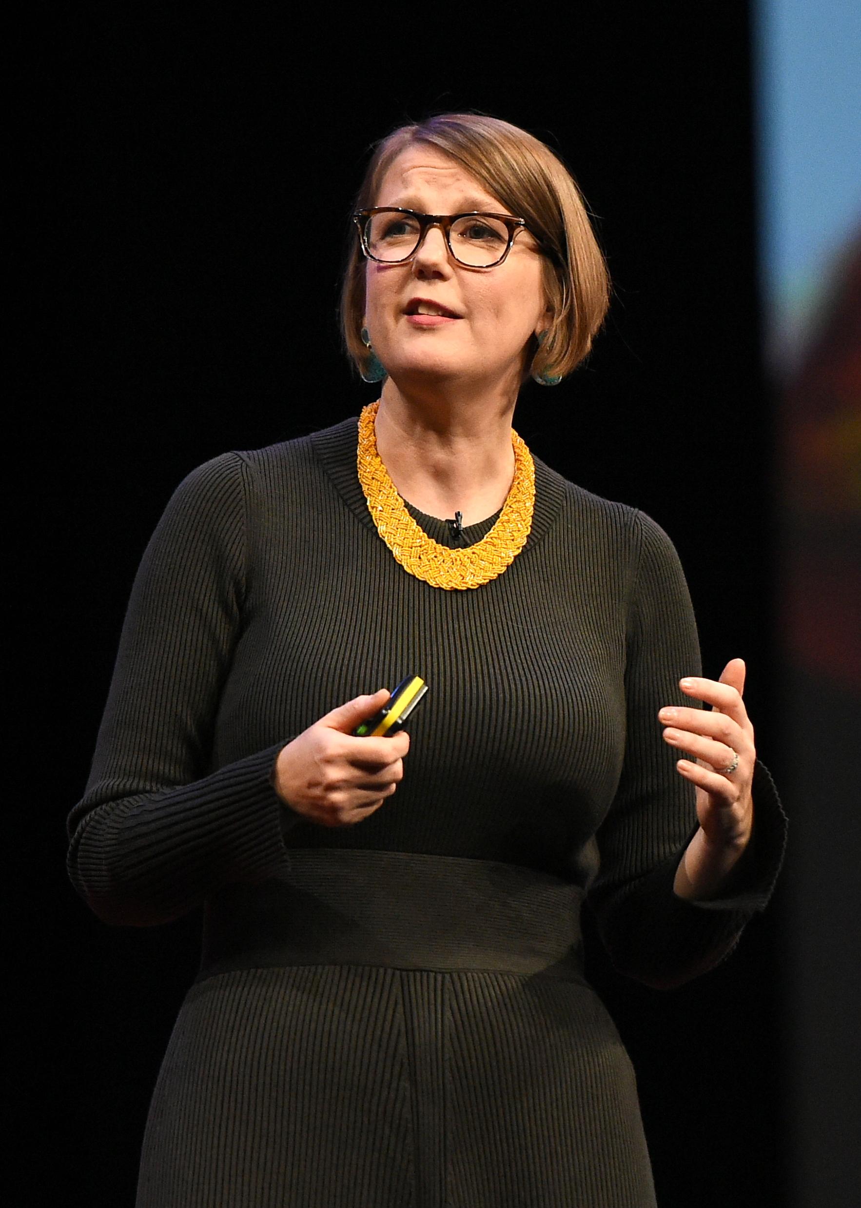 Lay Flurrie, mulher adulta, loira, cabelo curto, usando óculos e com vestido preto com gola amarela. Em pé, durante uma de suas apresentações em eventos.