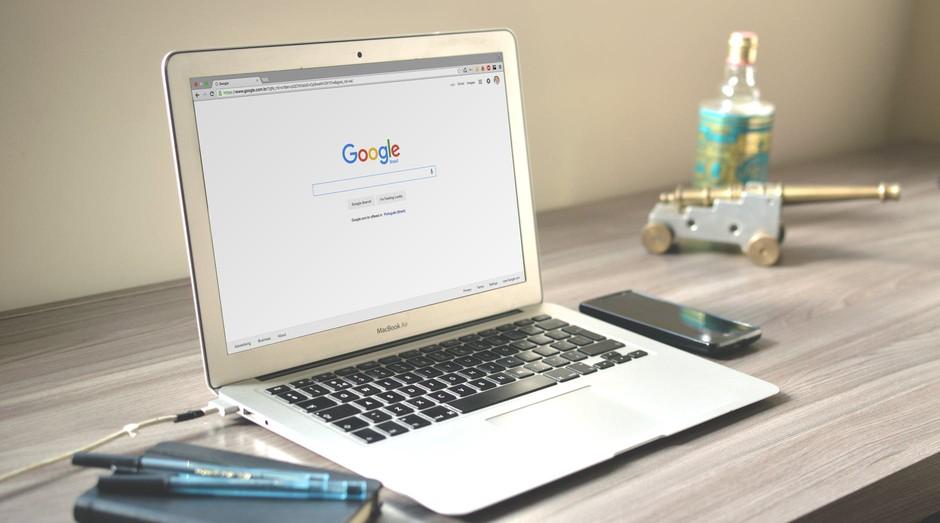 imagem de um notebook em cima de uma mesa de escritório, com caderneta e caneta do lado esquerdo e um celular do lado direito.