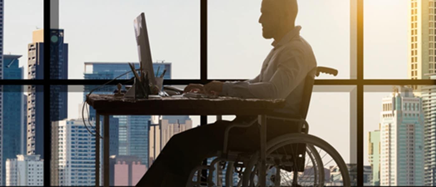 Homem em cadeira de rodas, sentado em frente a uma mesa de escritório com computador de mesa em frente. Ao lado, visão de outros prédios do bairro através de uma janela toda de vidro.